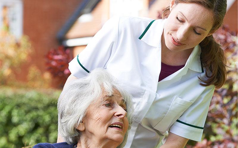 Seniorin im Rollstuhl mit Pflegerin