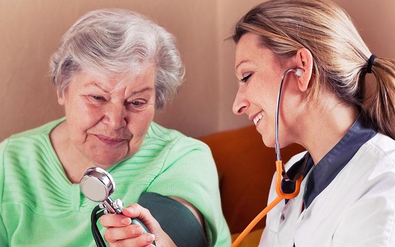 Pflegehelferin misst Blutdruck bei einer Seniorin