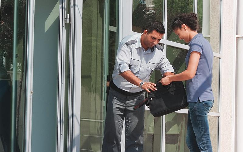 Sicherheitsfachkraft kontrolliert Tasche