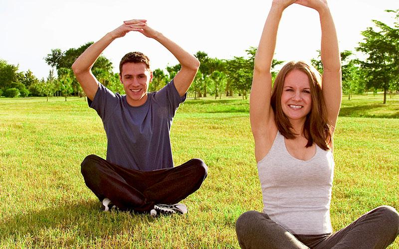 Mann und Frau machen Gymnastik auf der Wiese
