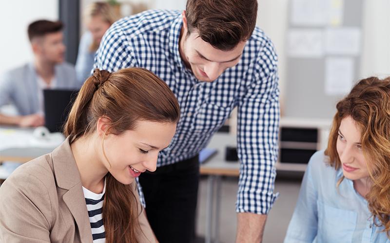 Mann hilft junger Frau bei der Umschulung