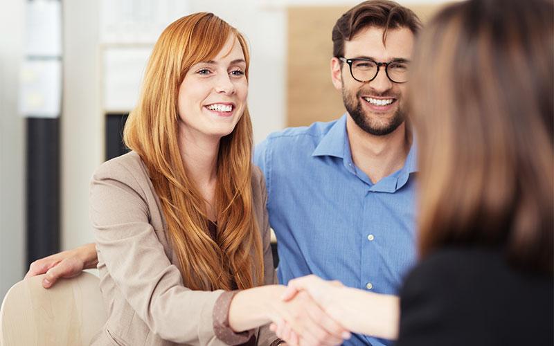 Beraterin schüttelt junger Frau die Hand